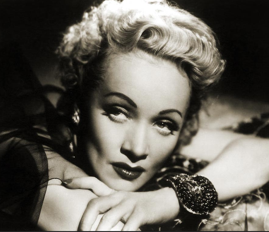 German-American actress MARLENE DIETRICH (1901 – 1992), who was born on December 27th. Her performance as Lola-Lola in The Blue Angel (1930), directed by Josef von Sternberg, brought her international fame and garnered her a contract with Paramount Pictures in the US. Hollywood films such as Shanghai Express (1932) and Desire (1936) capitalised on her glamour and exotic looks, cementing her stardom and making her one of the highest-paid actresses of the era. Dietrich became a U.S. citizen in 1939,[ and throughout World War II she was a high-profile frontline entertainer. Also in 1939, she played the cowboy saloon girl, Frenchie, in the light-hearted western Destry Rides Again, opposite James Stewart. It was a big hit. She played similar types in Seven Sinners (1940) and The Spoilers (1942), both opposite John Wayne. She followed with appearances for such distinguished directors as Alfred Hitchcock, Fritz Lang, Orson Welles, and Billy Wilder, in films that included A Foreign Affair (1948), Stage Fright (1950), Rancho Notorious (1952),