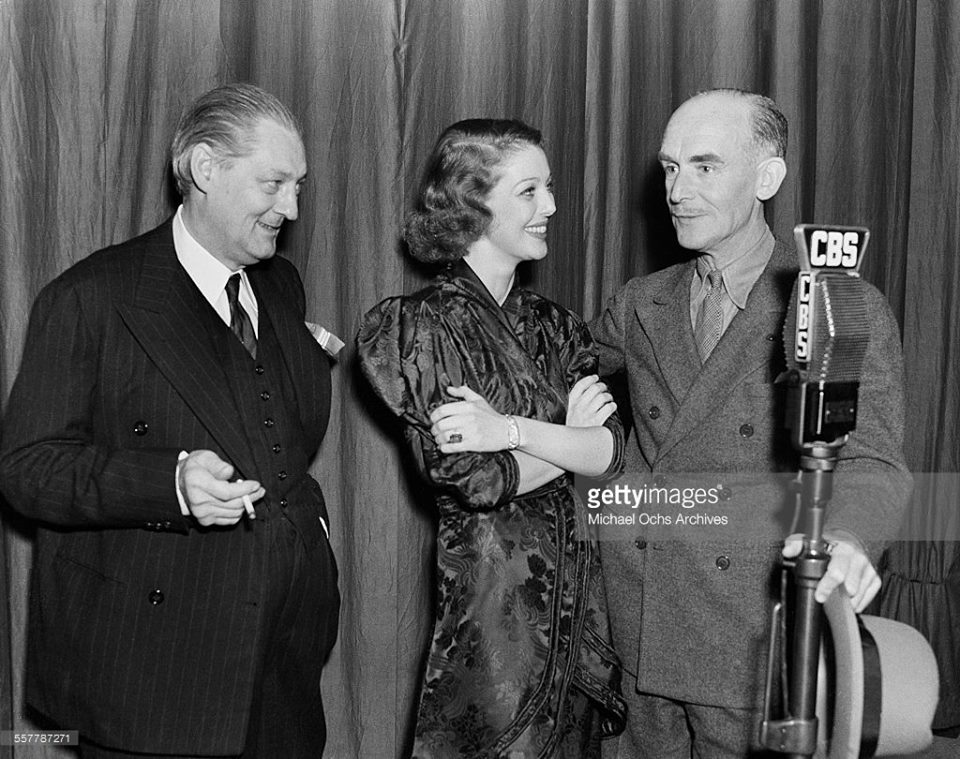 Actor Lionel Barrymore and actress Loretta Young stand with actor James Gleason at the microphone at CBS radio in Los Angeles, California.