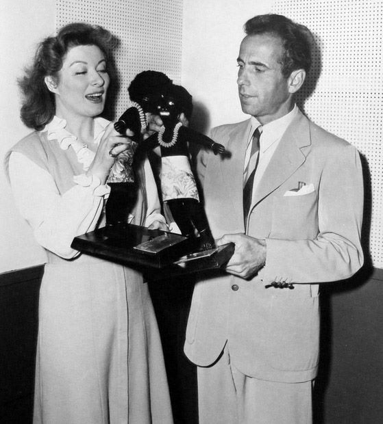 Greer Garson and Humphrey Bogart with Haitian dolls on NBC Radio´s The Army Hour. June, 1944