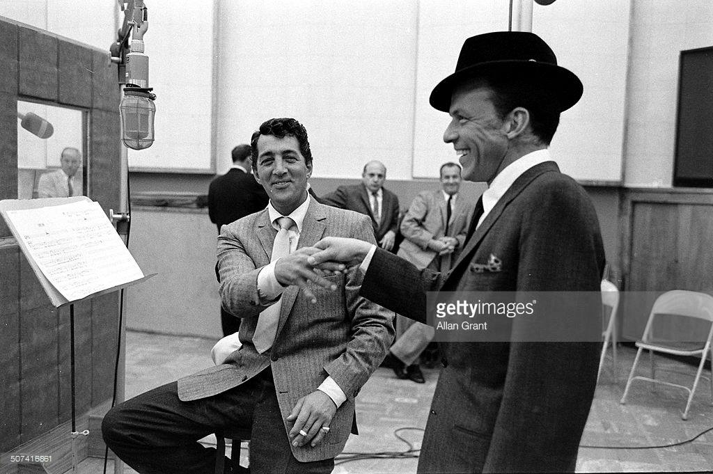 Dean Martin and Frank Sinatra share a laugh in a recording studio, 1958.