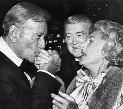 John Wayne greets Gloria Stewart, as Jimmy looks on.