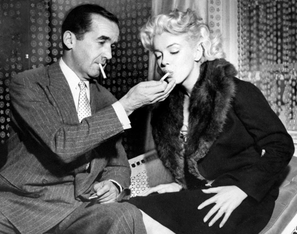 Edward R. Murrow lights a cigarette for Marilyn Monroe during interview on television show