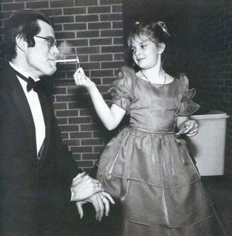 Stephen King receives a light from 9-year old Drew Barrymore