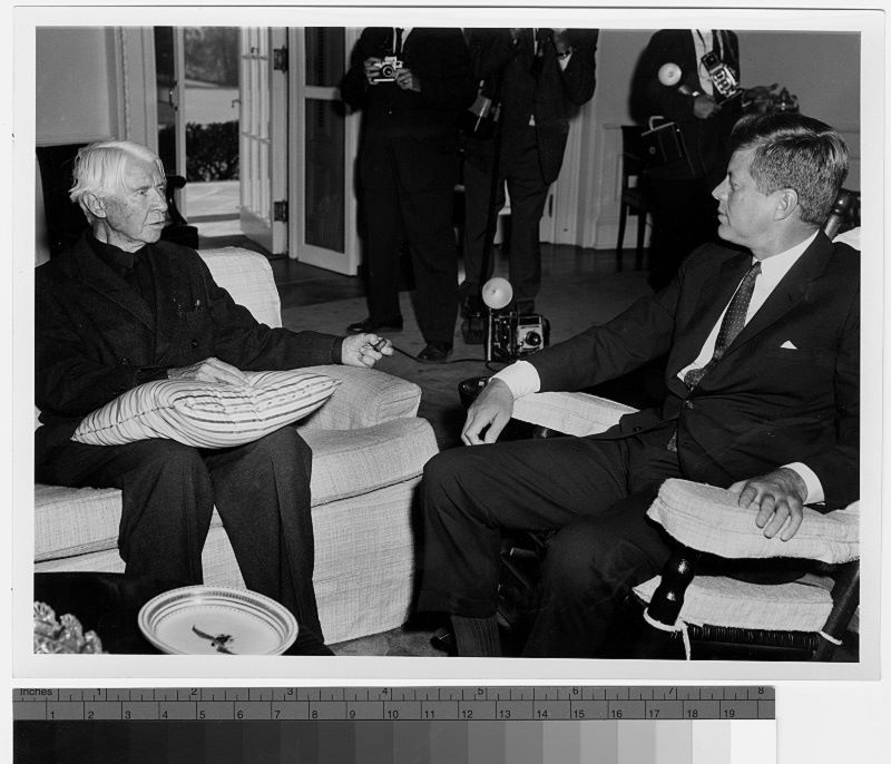 President John F. Kennedy sitting and talking with writer Carl Sandburg in a room at the White House.