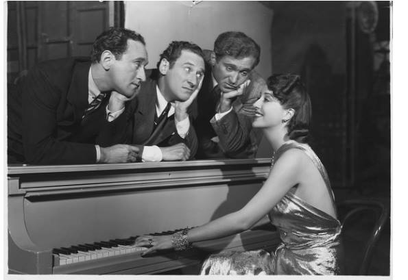 Gypsy Rose Lee plays piano for Jimmy, Al, and Harry Ritz (left to right) on the set of the 1937 film