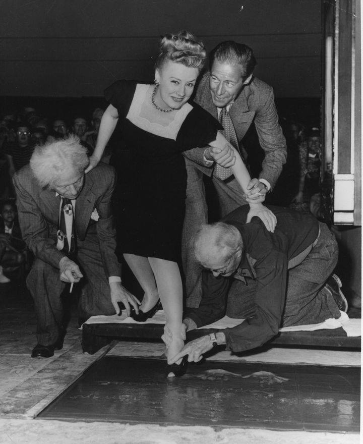 Irene Dunne & Rex Harrison leave their footprints at Grauman's Chinese Theatre today in 1946