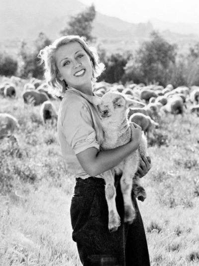 JOAN BLONDELL POSES WITH A LAMB.