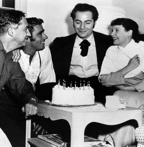 Director Mervyn LeRoy, Peter Lawford, Rossano Brazzi and June Allyson celebrate Brazzi's Birthday on the set of