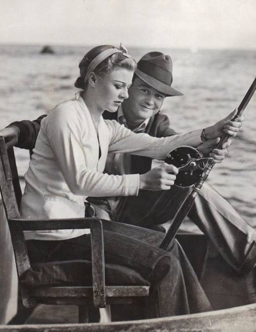 Lew Ayres teaching his bride-to-be Ginger Rogers how to fish