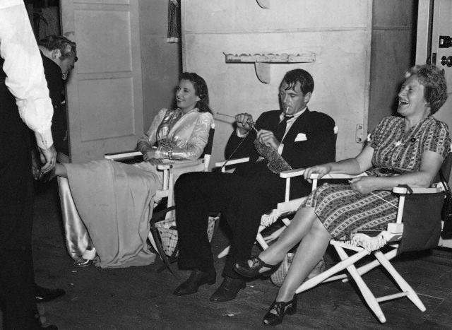 Barbara Stanwyck with Gary Cooper, who is knitting, behind the scenes of shooting