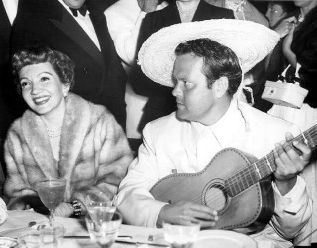 Orson Welles serenading lovely Claudette Colbert
