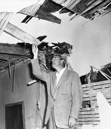 Dennis O'Keefe incredulously inspects the damage to his neighbor across the street. His neighbor's house was one of those destroyed when Howard Hughes famously ran out of petrol over Brentwood in 1946.