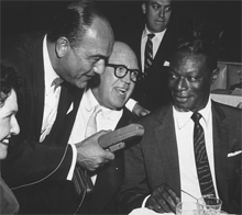 Larry Finley (holding recorder) in an impromptu interview of Nat King Cole, Jimmy McHugh and Louella Parsons at Ciro's on Wilshire Blvd. circa 1955.