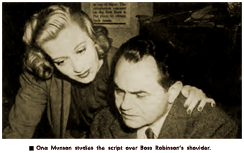 Caption reads - 'Ona Munson studies the script over Boss Robinson's shoulder.