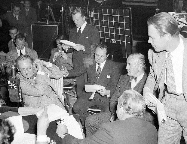 CA- Lionel Barrymore (L, hands to ear), James Cagney (standing, reading), Edward G. Robinson (center, seated), Donald Crisp (wearing bow tie, beside Robinson), Wayne Morris (right, standing), and Walter Connolly (back to camera) concentrate on the broadcast rehearsal