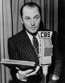 Brian Aherne at CBS mike holding scripts for The Saint from 1945