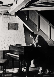 Britten puzzles over a composition at his piano, circa 1947