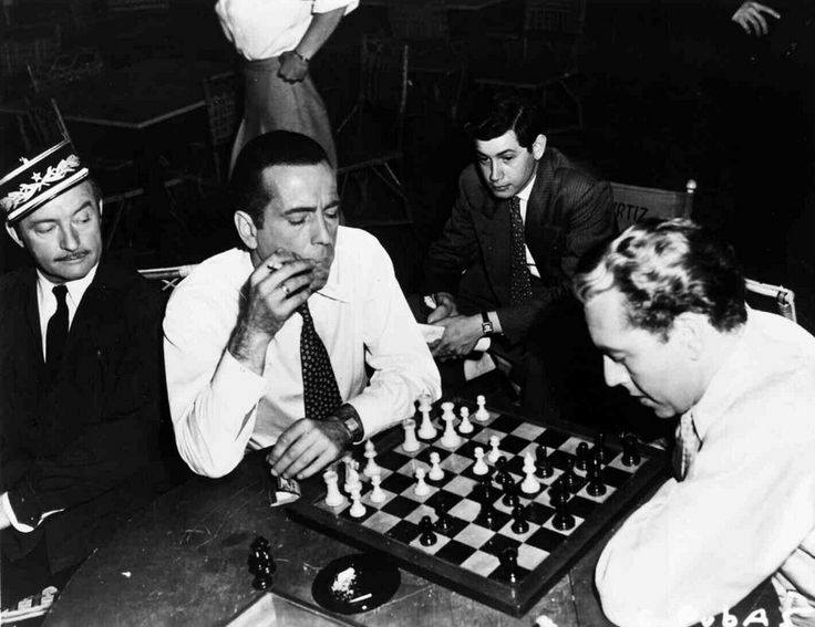 Claude Rains watches Humphrey Bogart and Paul Henreid play chess on the set of Casablanca.