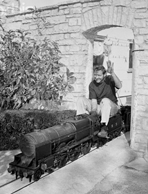 Rose's second great passion--Trains. Here riding his own miniature gauge train around his Sherman Oaks home, ca. 1942