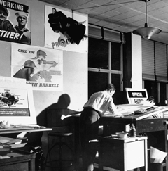 A draftsman burns the midnight oil in the poster room of the Office of War Information circa 1942