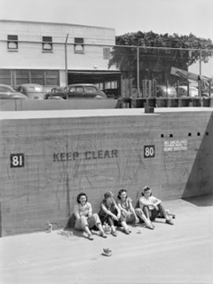 A group of 'Rosie Riveters' takes a lunch break at the Vega plant in Burbank, below an appropriately positioned 'KEEP CLEAR' notice.