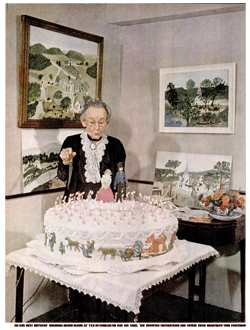 Grandma Moses blows at the candles on the huge birthday cake decorated with elements of her signature paintings.
