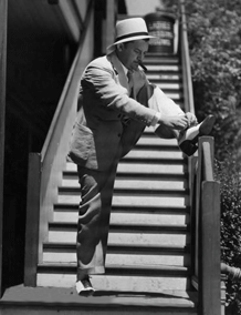 Jean Hersholt stops to retie his shoes at original Motion Picture Relief Fund Country Home, ca. 1939