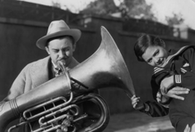 Jean Hersholt clowns with an old euphonium at the original Motion Picture Relief Fund Country Home, ca. 1939