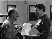 Jean Hersholt stops to go over some paperwork with Jimmy Durante at original Motion Picture Relief Fund Country Home, ca. 1939