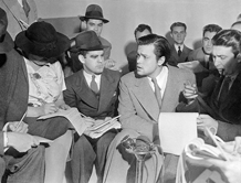 Welles is quizzed by reporters after The War of the Worlds broadcast.