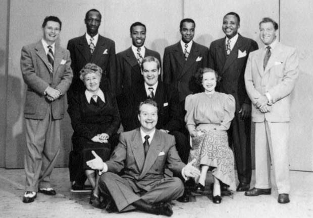 Photo of 1948 Raleigh Cigarettes Program radio cast: Standing: Pat McGeehan, The Four Knights, David Rose (orchestra leader). Seated:Verna Felton (