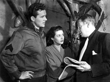 Film Corporal Howard Duff in impromptu script conference with his producer/mentor, Mark Hellinger and Yvonne DeCarlo, for Brute Force (1947). Duff was credited as 'Howard Duff, Radio's Sam Spade'