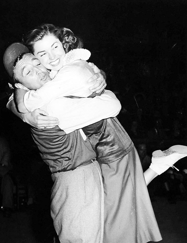 Robert Mitchum gives a big hug to Esther Williams