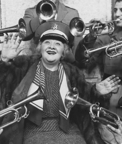Trumpeters surround singer and actress Sophie Tucker as she arrives in Chicago in 1934.