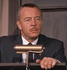 Closeup of Tremayne, exasperated by Cary Grant's erratic bidding in North by Northwest, (1959)